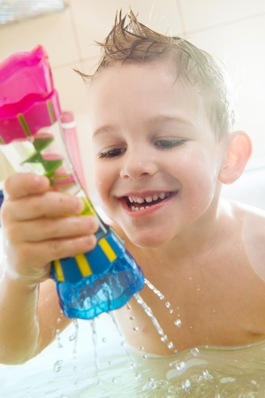 Happy little boy bathing in bathtub at home photo
