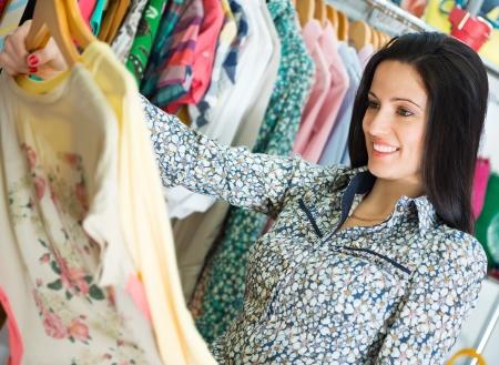 kledingwinkel: Lachende jonge mooie brunette winkelen in winkelcentrum