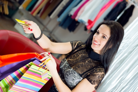 Beautiful smiling young girl shopping with credit card photo