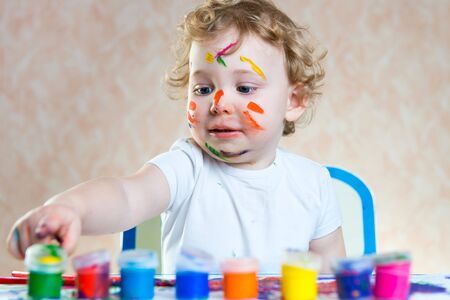 a small painting: Cute little child painting with paintbrush and colorful paints