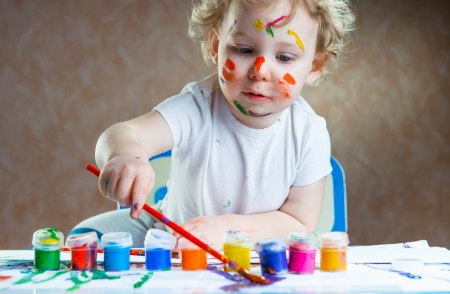 children painting: Cute little child painting with paintbrush and colorful paints