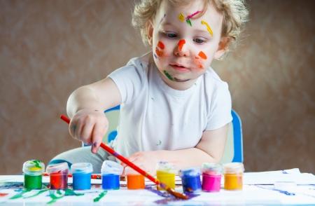 ni�os pintando: Pintura lindo ni?o peque?o con pincel y pinturas de colores
