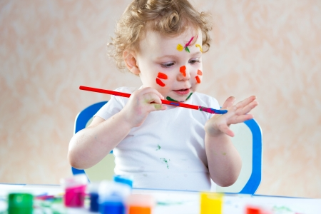 Cute little child painting with colorful paints photo