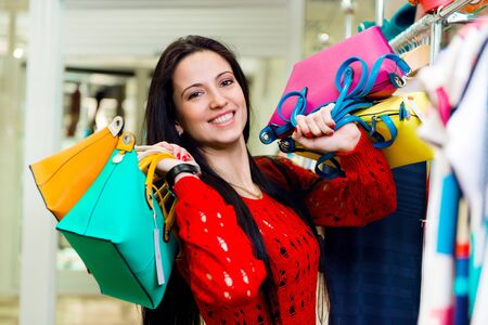 Beautiful smiling young girl with shopping bags in mall photo
