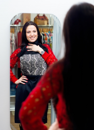 fitting: Pretty young girl trying new dress in fitting room