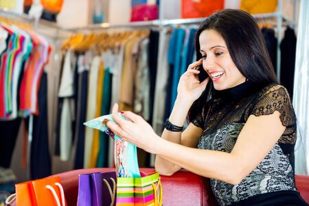 Beautiful young brunette girl talking via phone in clothes boutique Stock Photo - 19098305