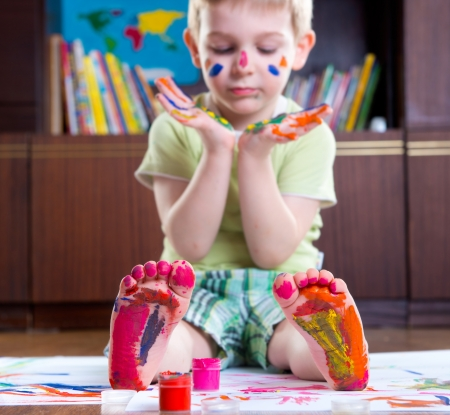 Cute happy boy with colorful  painted hands and foot photo