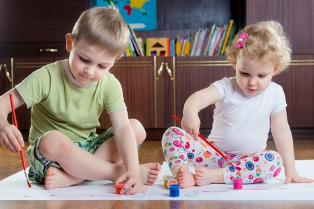 Cute brother and sister painting with colorful paints photo