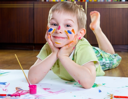 play room: Excited little boy painting with colorful paints Stock Photo