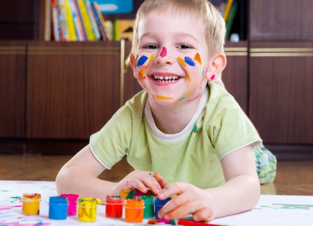 Excited little boy painting with colorful paints photo