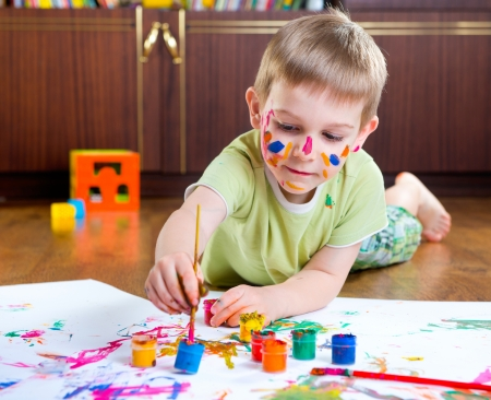 Cute little boy painting on floor at home photo