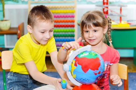 human geography: Cute little brother and sister study globe