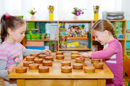 playing a game: Two little girls playing in checkers in kindergarten Stock Photo