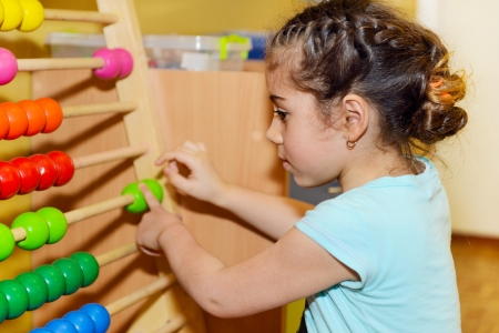 Cute little girl playing with abacus in kindergarten photo