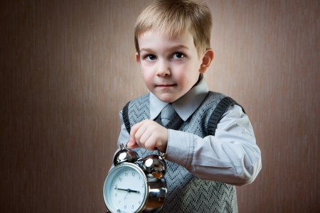 Cute little blond boy holding alarm clock photo