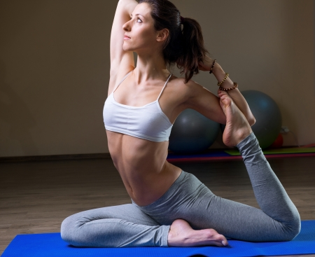Young woman training in yoga asana in gym