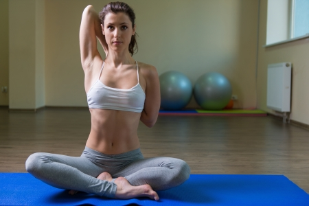 Young woman training yoga in gym photo