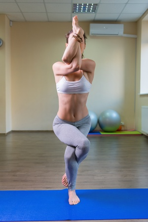 Beautiful young woman standing in yoga asana photo