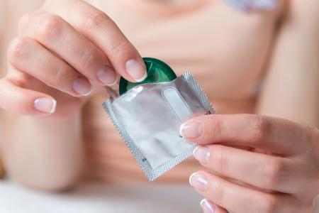 sexual education: Joven mujer con condón en buena parte