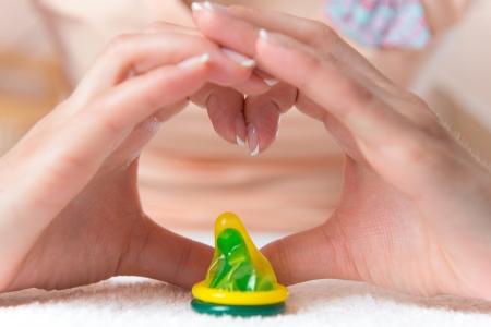 educacion sexual: Condón en el corazón haciendo por manos de mujer Foto de archivo