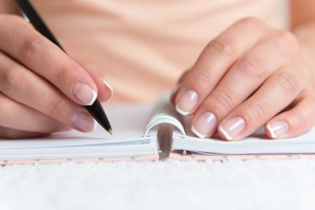 journal intime: Jeune femme est en train d'�crire des notes et la planification de son horaire Banque d'images