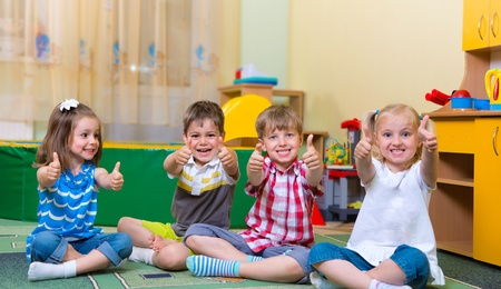 Group of excited children holding thumbs up