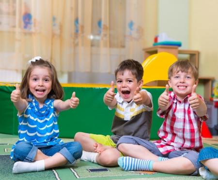 Groep opgewonden kinderen die duimen omhoog Stockfoto
