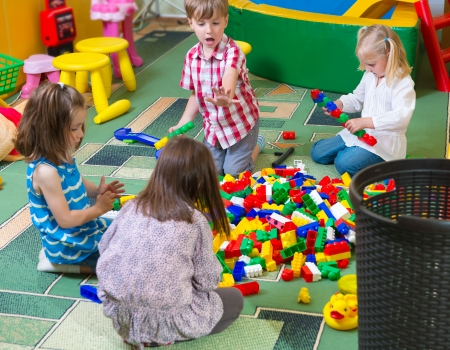 nursery room: Group of kids playing with colorful constructor on floor