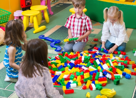 kindergarten toys: Group of kids playing with colorful constructor on floor