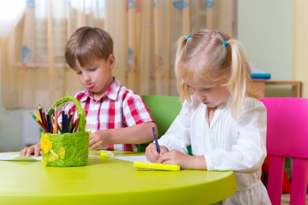 Two cute little prescool kids drawing with crayons at the table photo