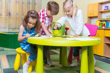Group of cute little prescool kids drawing with crayons at the table photo