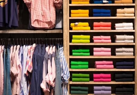 kledingwinkel: Verschillende kleuren shirts bij plank in winkel