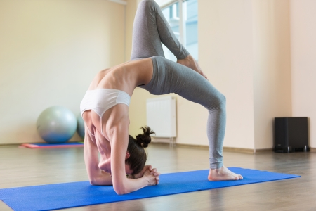 Pretty young woman yoga workout in gym photo