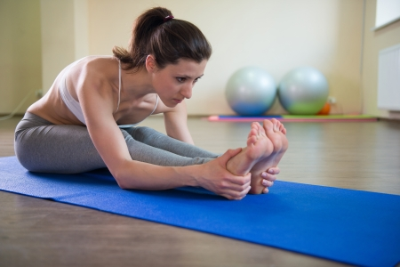 mat: Young pretty girl stretching legs. Yoga workout Stock Photo