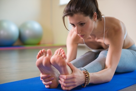 foot model: Young pretty girl stretching legs. Yoga workout Stock Photo