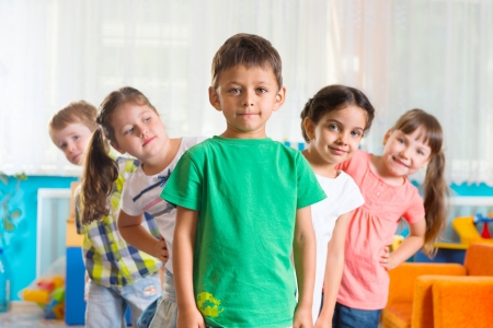 Group of five preschoolers standing in playroom