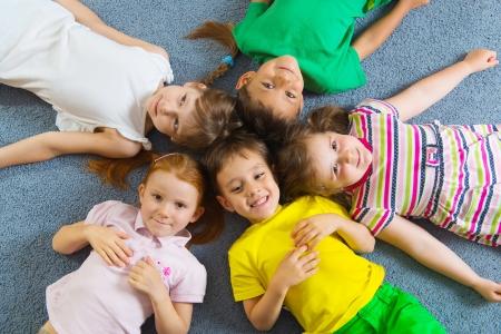 Lindos niños acostados en el piso en el jardín de infantes