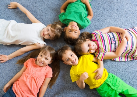 preschool children: Cute little children lying on floor in kindergarten
