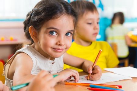 カラフルな鉛筆で描くかわいい小さな prescool の子供たちのグループ