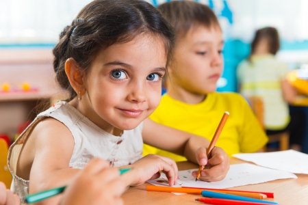 Group of cute little prescool kids drawing with colorful pencils photo