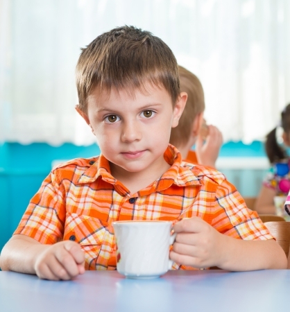 Cute little child drinking milk at kindergarten photo