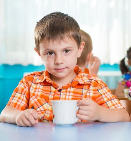 ni�os comiendo: Poco de leche potable ni�o lindo en el jard�n de infantes Foto de archivo