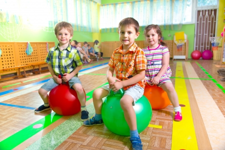 physical: Cute children playing in kindergarten gym Stock Photo