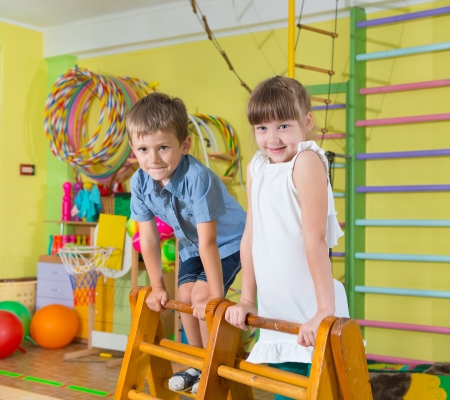 gym girl: Cute children playing in kindergarten gym Stock Photo
