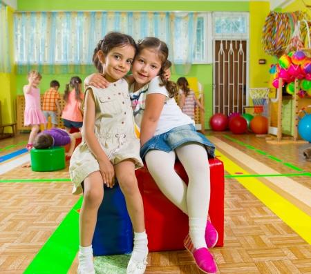 friendship: Enfants mignons jouant dans le gymnase de l'école maternelle