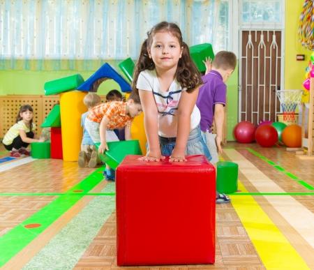 ni�as jugando: Los ni�os lindos que juegan en el gimnasio de kindergarten