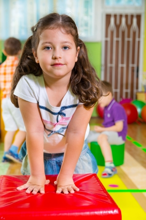 physical education: Cute children playing in kindergarten gym Stock Photo