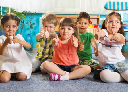 niños sentados: Cinco niños que se sientan en el suelo con los pulgares para arriba signo