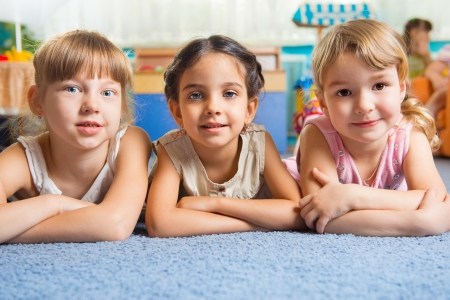 Three beautiful girls lying on floor at daycare photo