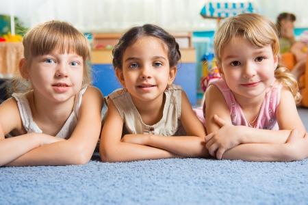 Tres chicas guapas tumbado en el suelo en la guardería Foto de archivo - 20085559